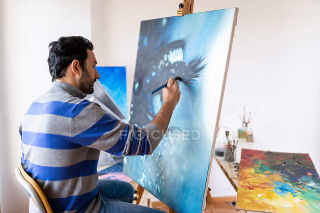 Side view of young bearded ethnic painter in casual wear siting in a chair painting with brush on canvas in art studio — Stock Photo