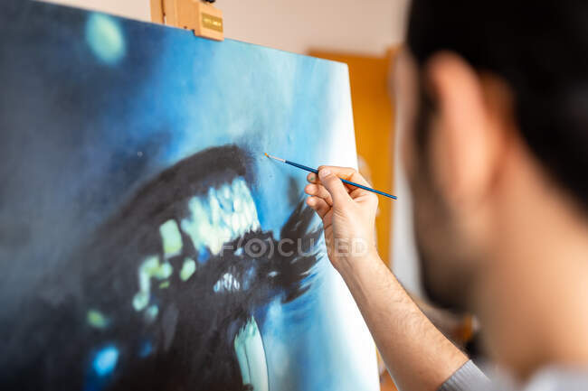 Side view of cropped unrecognizable painter in casual wear painting with brush on canvas in art studio — Foto stock