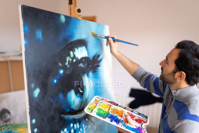 Side view of young bearded ethnic painter in casual wear painting with brush on canvas in art studio — Foto stock
