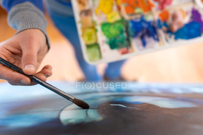 From above cropped unrecognizable painter in casual wear painting with brush on canvas in art studio — Stock Photo