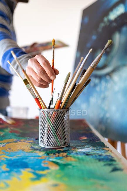 Crop anonymous male painter taking paint brush from glass near painting representing eye in workroom — Foto stock