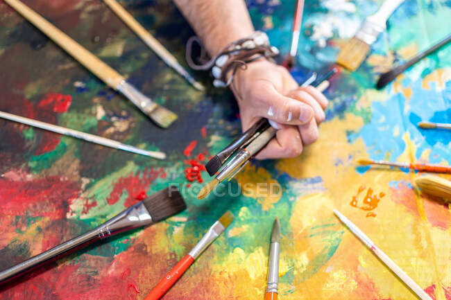 Top view of crop anonymous male painter with collection of professional tools on bright painted picture — Stock Photo