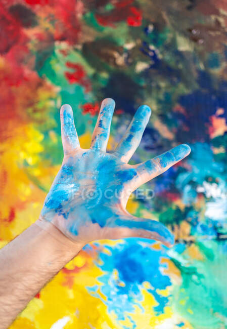 Artist with open hand showing palm with blue paint near colorful canvas in studio - foto de stock