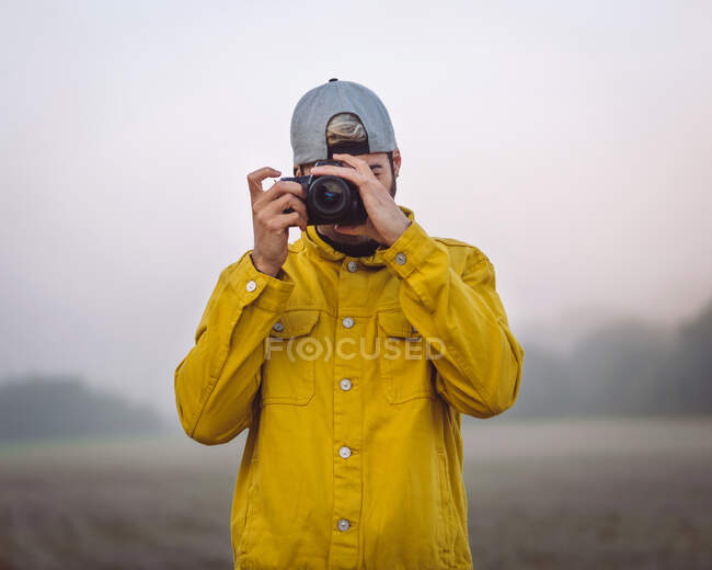 Young male photographer in yellow denim jacket taking photo on photo camera while standing on foggy blurred nature background - foto de stock