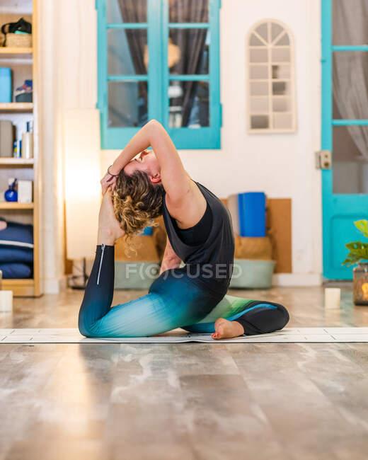 Вид сбоку спокойной женщины в костюме одноногого голубя во время занятий йогой в студии в дневное время — стоковое фото