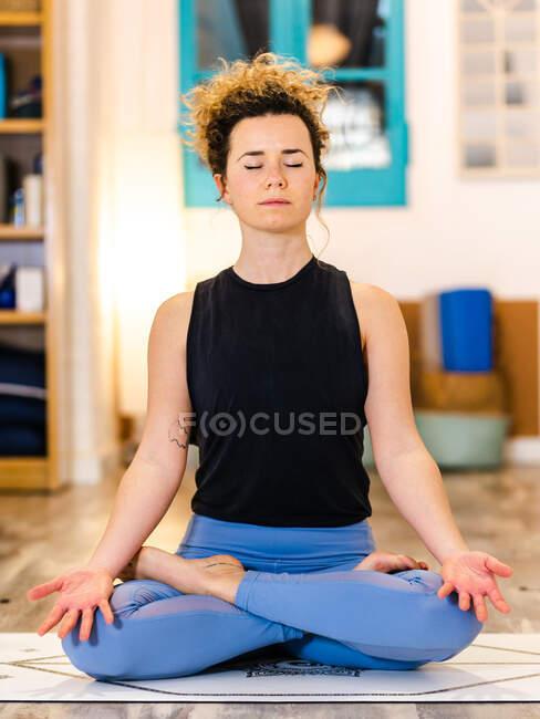 Спокойная женщина в активной одежде, сидя на коврике и Lotus позировать, практикуя йогу в легкой студии — стоковое фото