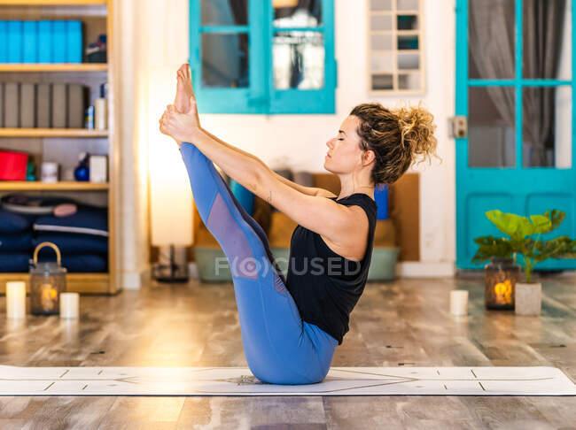 Konzentrierte Frau mit geschlossenen Augen in Aktivkleidung beim Bootsposieren während der Yoga-Praxis im Studio tagsüber — Stockfoto