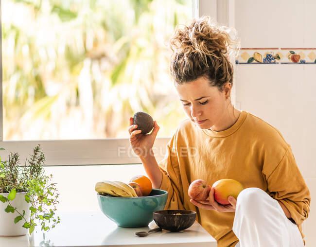 Jovem pensativa com cabelo encaracolado em roupas casuais sentada à mesa e escolhendo frutas frescas para o café da manhã saudável em casa à luz do dia — Fotografia de Stock