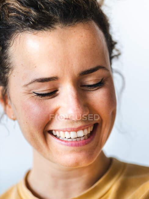 Donna positiva in abiti casual sorridente con gli occhi chiusi contro la parete chiara sfocata in appartamento — Foto stock