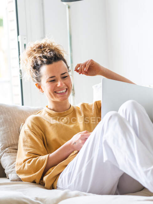 Positive young woman with curly hair in casual clothes sitting on comfortable sofa and browsing netbook in light apartment in daytime — Stock Photo