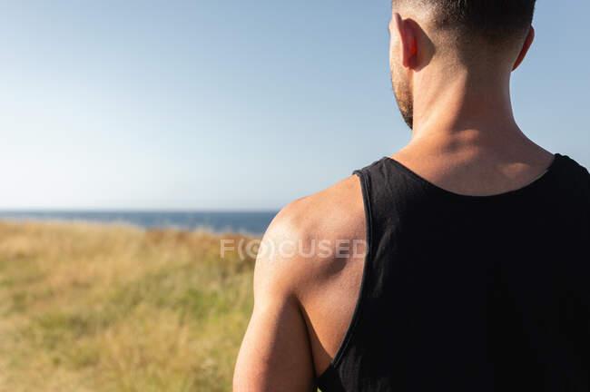 Deportista masculino determinado con fuerte torso de pie en la colina cubierta de hierba en el día soleado en verano y mirando hacia otro lado - foto de stock