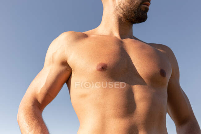 Deportista masculino determinado con fuerte torso desnudo de pie en la colina cubierta de hierba en el día soleado en verano y mirando hacia otro lado - foto de stock