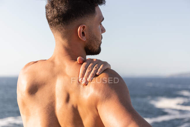 Back view of male bodybuilder with muscular naked torso warming up and stretching arms before workout near sea in summer — Stock Photo