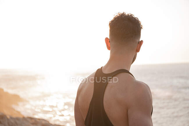 Back view of muscular male athlete in sportswear standing on beach and enjoying sundown after training in summer — Stock Photo