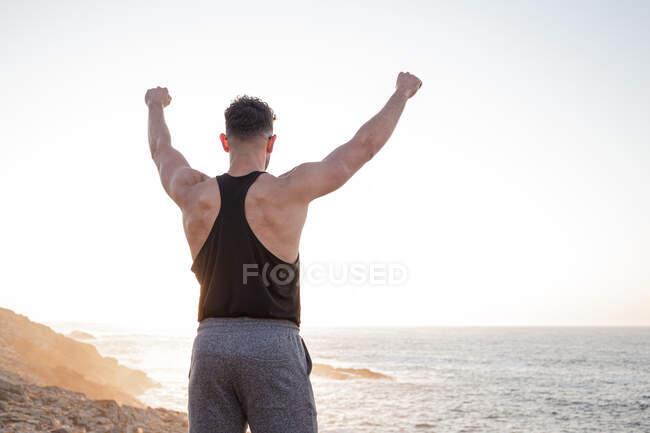 Вид сзади на мускулистого спортсмена в спортивной одежде, стоящего на пляже и наслаждающегося закатом после тренировки летом — стоковое фото