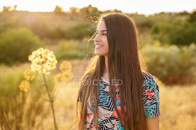 Нежная улыбающаяся женщина, стоящая в поле возле растения Анжелика, наслаждаясь солнечным днем весной — стоковое фото