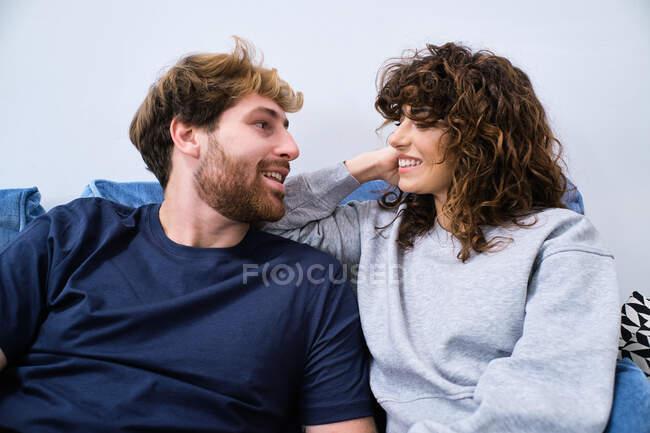 Glückliches junges Paar in lässiger Kleidung sitzt auf der Couch und schaut sich an, während sie Zeit miteinander verbringen — Stockfoto