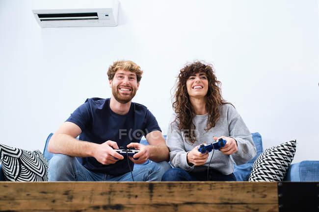 Внизу веселые и возбужденные молодые пары в повседневной одежде играют в видеоигры на консоли в стильной гостиной — стоковое фото