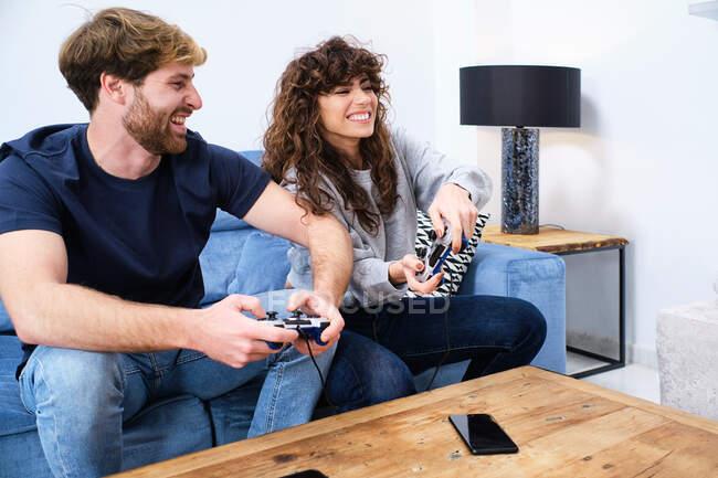 Вид сбоку веселой и взволнованной молодой пары в повседневной одежде, играющей видеоигру на консоли в стильной гостиной — стоковое фото