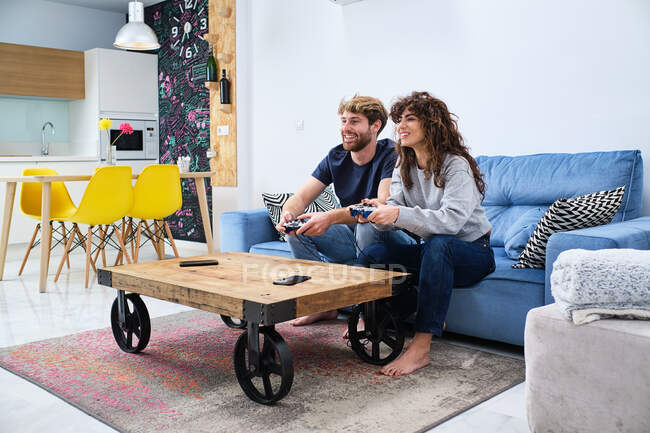 Side view of cheerful and excited young couple in casual clothes playing video game on console in stylish living room — Stock Photo