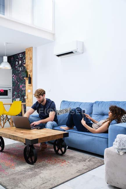 Молодая женщина просматривает планшет лежа на диване в то время как мужчина серфинг интернет на ноутбуке в современной квартире — стоковое фото