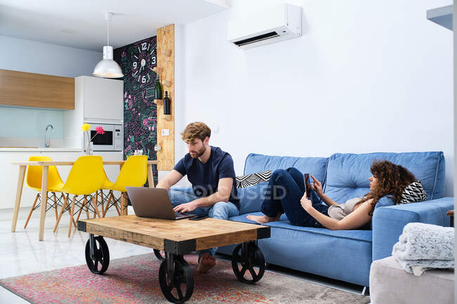 Jeune femme naviguant tablette couché sur le canapé tandis que l'homme surfant sur Internet sur ordinateur portable dans un appartement moderne — Photo de stock