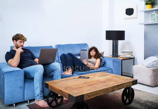 Young woman browsing tablet lying on sofa while man surfing internet on laptop in modern apartment — Stock Photo