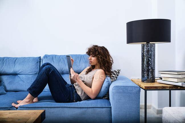 Side view of young female with curly hair wearing casual clothes lying on blue sofa and browsing tablet in living room — Stock Photo