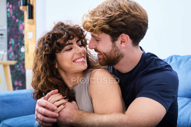 Happy young couple in casual clothes sitting on couch and looking at each other while spending time together — Stock Photo
