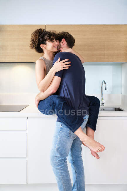 Вид сбоку на молодую пару в повседневной одежде, нежно обнимающуюся на светлой кухне на прилавке — стоковое фото