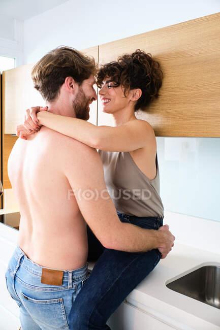 Бічний погляд на молоду пару у звичайному одязі, який ніжно обіймає на кухні за прилавком. — стокове фото