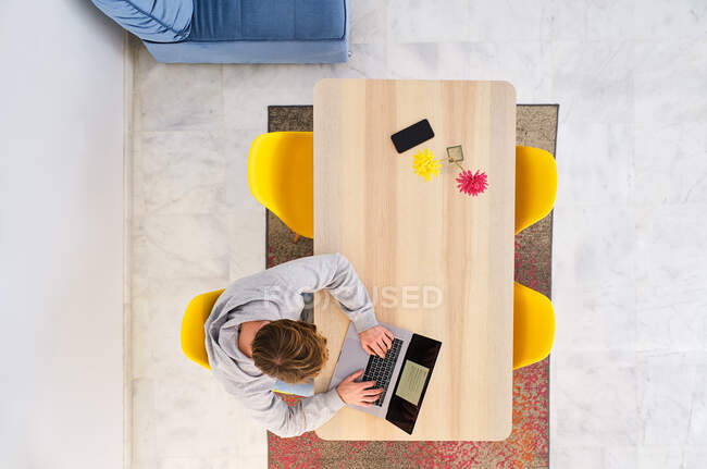 From above of anonymous male in casual clothes sitting on chair near table and using laptop in light apartment — Stock Photo
