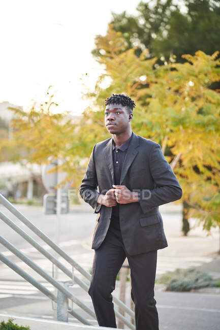 Positive young African American male wearing black classy suit going upstairs in city park and looking away — Stock Photo