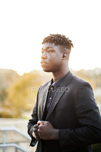 Side view young African American male with dreadlocks wearing classy black suit standing on blurred park background — Stock Photo