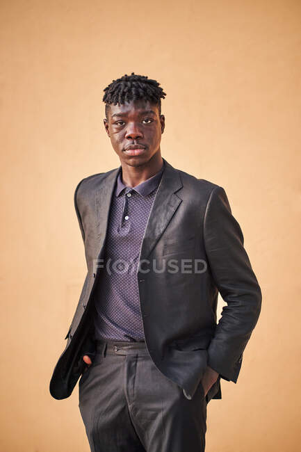 Self assured young African American male wearing classy black suit standing with hands in pockets against beige wall and looking at camera in studio — Stock Photo