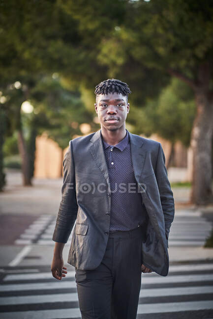 Calm young African American male with dreadlocks wearing classy black suit standing on blurred park background and looking at camera — Stock Photo
