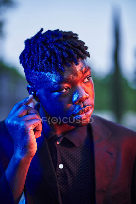 Contemplative young African American male in stylish clothes putting on wireless earbuds and looking away while standing on evening street — Stock Photo