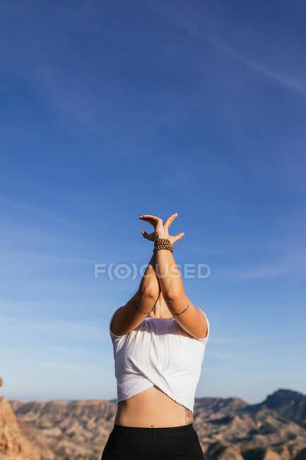 Тонкая неузнаваемая женщина в повседневной одежде, выступающая Гора с поднятыми руками и загнутой осанкой на склоне скалистой горы — стоковое фото