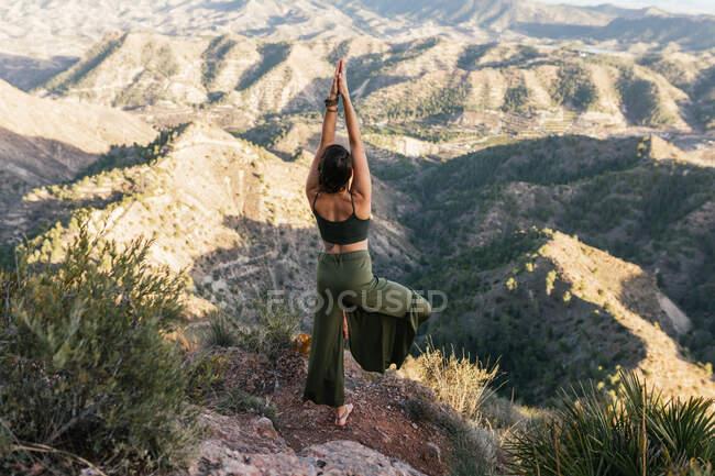 Задний вид неузнаваемой темноволосой женщины, стоящей на вершине скалистой горы и делающей
