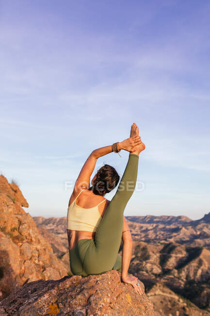 Flexible female in sportswear performing Heron pose on top of rocky hill while practicing yoga — Stock Photo