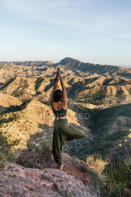 Back view of unrecognizable dark haired female standing on top of rocky mountain and doing Tree with Arms Up pose — Stock Photo