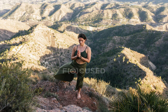 Young female standing on top of rocky mountain and doing Tree with prayer hands pose — Stock Photo