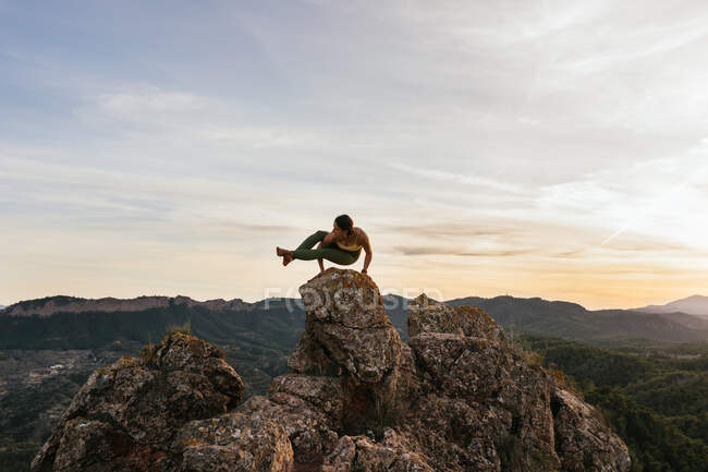 Confident young female performing Eight Angle posture on top of rocky mountain on height — Stock Photo