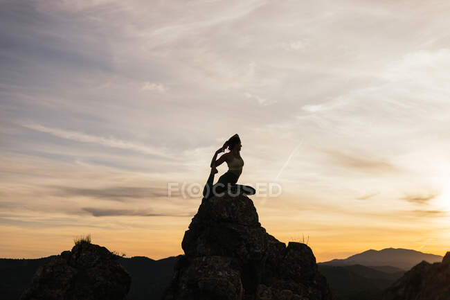 Silhouette of slim female performing One Legged King Pigeon pose on top of mountain at bright sundown — Stock Photo
