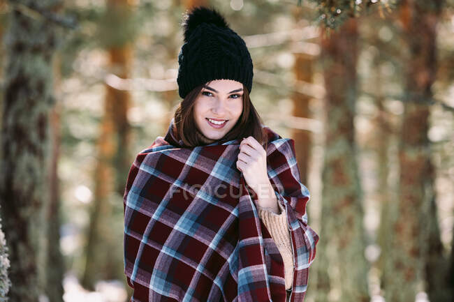 Content female wrapped in warm plaid standing in snowy woods and looking at camera — Stock Photo