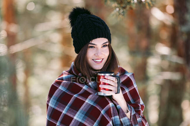 Female wrapped in warm plaid sitting on tree trunk in snowy winter forest and enjoying hot drink from cup — Stock Photo
