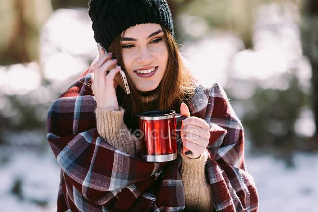 Веселая женщина, завернутая в теплую клетку, сидит на стволе дерева в зимнем лесу и разговаривает по мобильному телефону в солнечный день — стоковое фото