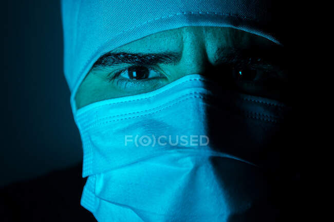 Closeup of male surgeon in medical mask looking at camera in dark room with blue neon light — Stock Photo