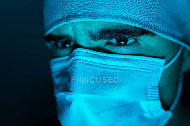 Closeup of male surgeon in medical mask looking away in dark room with blue neon light — Stock Photo