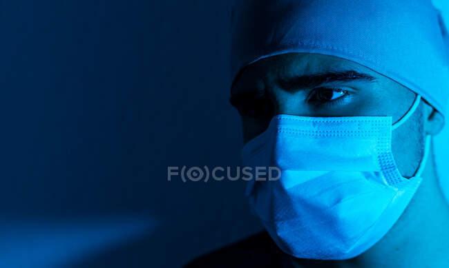 Großaufnahme eines männlichen Chirurgen in medizinischer Maske, der in einem dunklen Raum mit blauem Neonlicht wegschaut — Stockfoto
